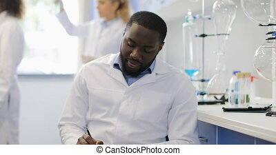 Female Scientist Discuss Test Tube With African American Colleague While Researchers Team Making Experiment In Lab
