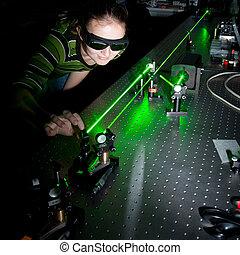 female scientist doing research in a quantum optics lab -...