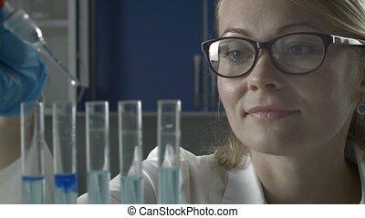 Female scientist dropping liquid into test tubes