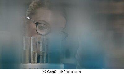 Female scientist examining test tube in lab