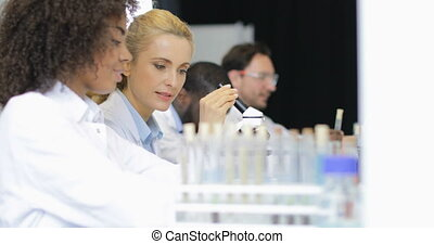 Female Scientist Explain Assistant Result Of Experiment Working With Microscope Over Team Of Researchers In Modern Laboratory
