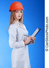 female scientist in helmet with pen and paper