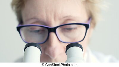Female scientist looking through microscope - Mid age female...