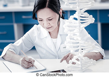 Female scientist taking notes while working on healthcare...