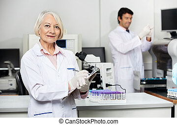 Female Scientist Writing On Clipboard In Laboratory