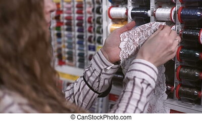 Female seamstress with wavy hair selects the thread of white...