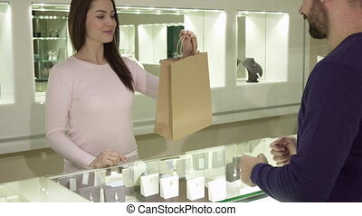 Female seller gives customer his purchase at the jewelry shop