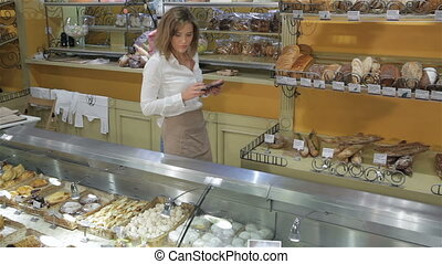 Female seller walks along the showcases