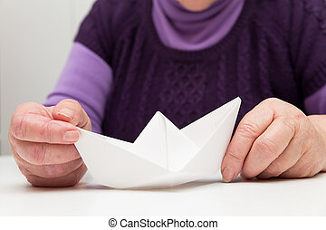 senior adult with a paper boat