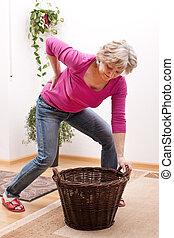 Senior has back pain due to heavy load - female Senior has...