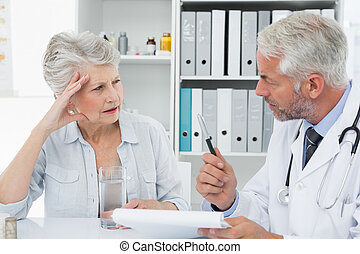 Female senior patient visiting a doctor at the medical ...