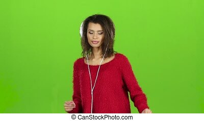 Female sexually dances with headphones on green screen. Slow motion