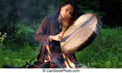 Female shaman performs a shamanic rite with a tambourine while in a trance by the fire in the forest