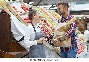 Female Shop Assistant Talking to Customer
