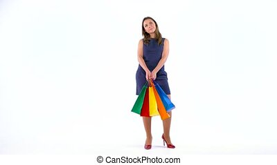 Female shopper holding multicolored shopping bags on white background in studio. Let's go shopping concept