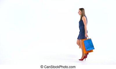 Female shopper holding multicolored shopping bags on white...