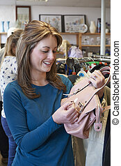 Female Shopper In Thrift Store Looking At Handbag