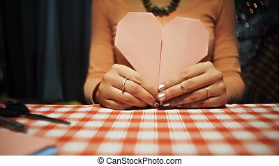 Female showing origami heart from pink paper to camera