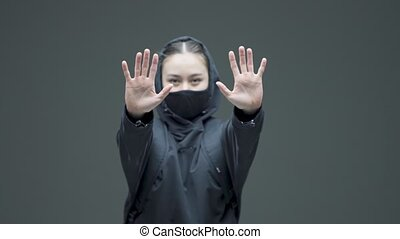 Female shows defensive distancing hand gesture. Gender, racial discrimination protest, fight for womens rights. High quality 4k footage
