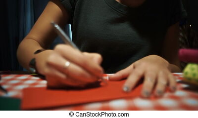 Female sighning a red postcard for holiday