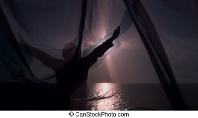 Female silhouette at sunset through a transparent curtain