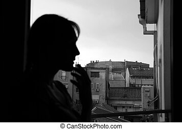 woman silhouette looking out window indoors, black and white