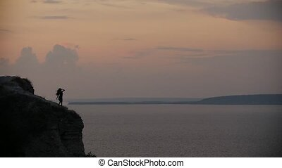 Female silhouette dancing on the edge of the cliff at sunset
