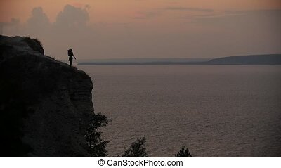 Female silhouette in black dress dancing on the edge of the cliff by the sea at sunset
