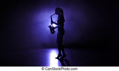 Female silhouette in smoky studio plays on saxophone. Slow motion