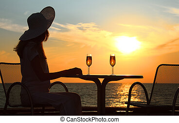 Female silhouette on sunset behind  table with two glasses
