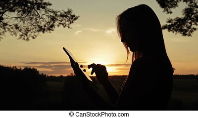 Female silhouette using a digital tablet in the forest at sunset
