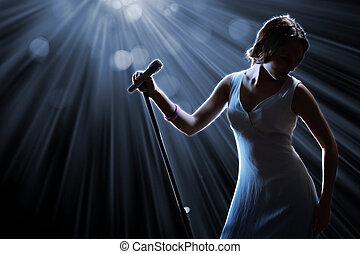 Female singer on the stage holding a microphone