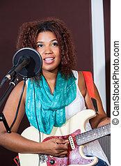 Female Singer Playing Guitar In Studio