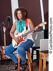 Female Singer Playing Guitar While Sitting On Stool
