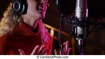 Female singer singing in a music studio - Front view close ...