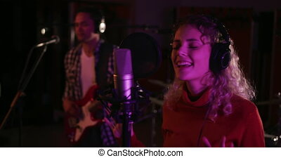 Female singer singing in a music studio