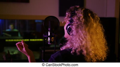Female singer singing in a music studio - Rear view close up...