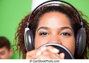 Female Singer Wearing Headphones While Performing - Portrait...