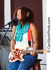Female Singer With Eyes Closed Playing Electric Guitar