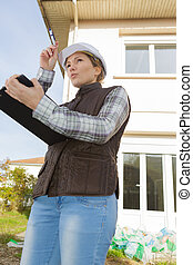 female site builder holding a clipboard