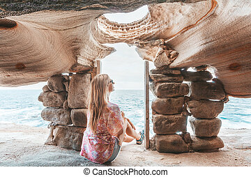 Female sits inside cliff top cave watching the ocean