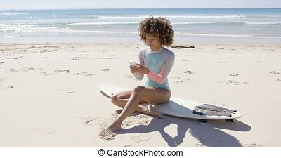 Female sitting on beach using smartphone
