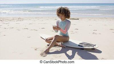 Female sitting on beach using smartphone