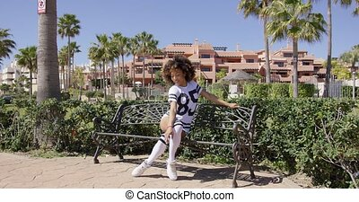 Female sitting on bench on sidewalk wearing white sportive outfit and knee-high socks.