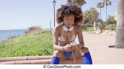 Female sitting on curb with headphones