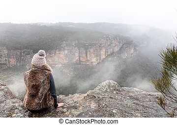 Female sitting on mountain top cliff ledge looking out into the misty fog