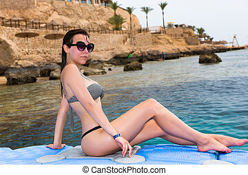 Female sitting on pontoon in front of the beautiful and clean sea