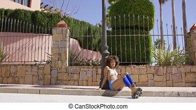 Female sitting on sidewalk