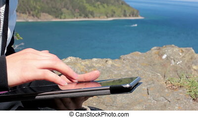 Female sitting on the shore of Lake Baikal on a rock and using a tablet