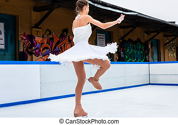 Female skater dancing on ice rink